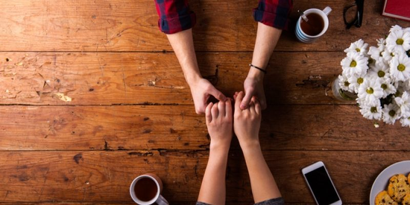Couple holding hands on wood table