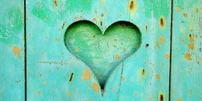 Heart carved into teal aged wood