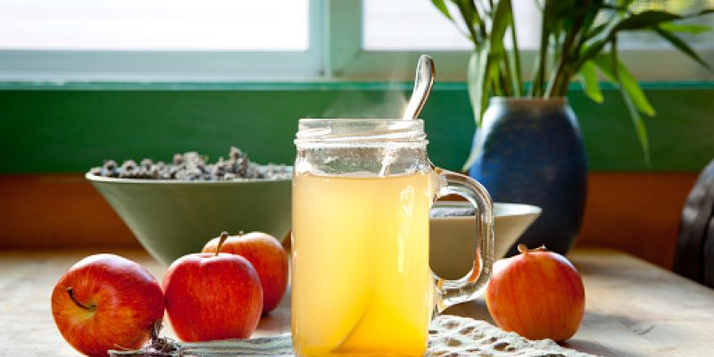 Hot apple cider vinegar and honey drink with apples on a table