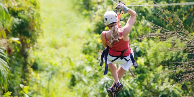 Woman ziplining in bright jungle