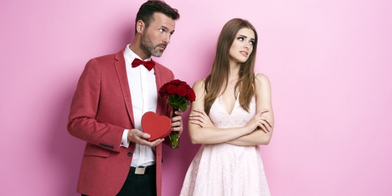 Man offering woman flowers and chocolate. Woman is disdainful.