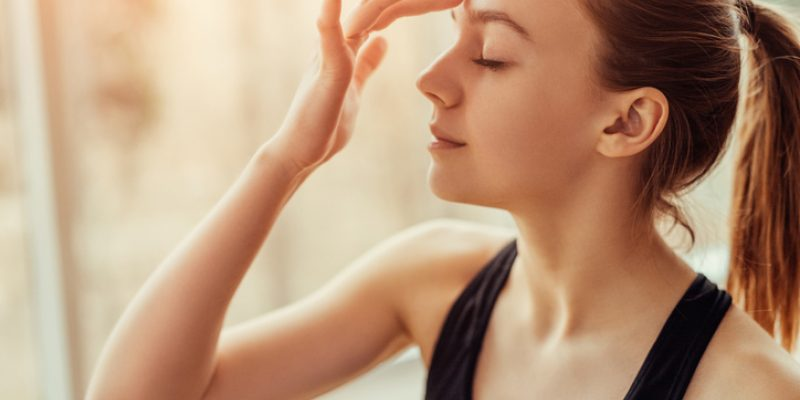 Woman touching third eye on forehead
