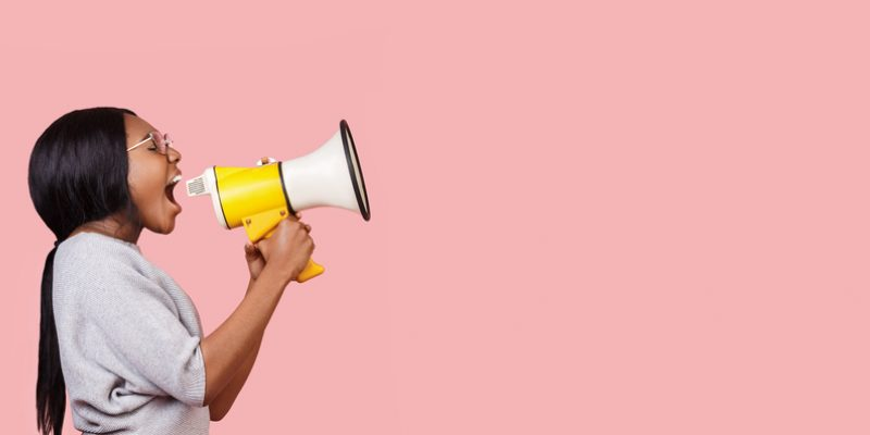 A young woman is using affirmations for speaking your truth, expressed with a photo of a bullhorn.