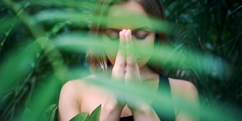 young woman meditating and doing namaste hand in jungle