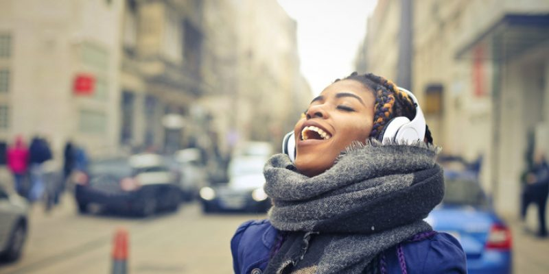 Woman walking down a city street listening to music and practicing vocal yoga