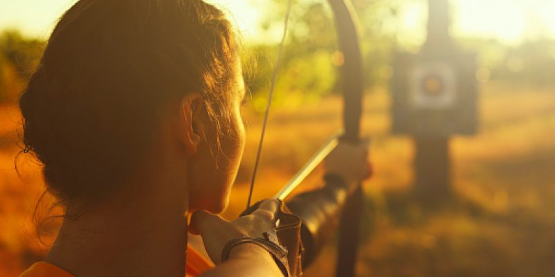 Woman with a bow and arrow aiming at bullseye target