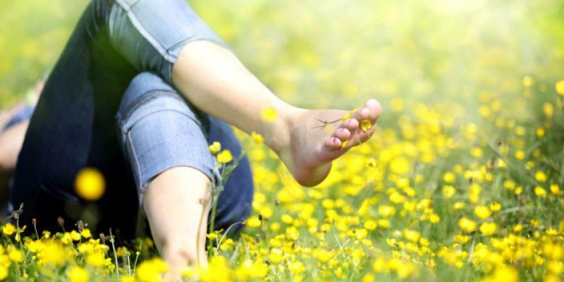 Barefoot woman lying in grass