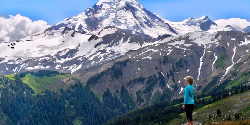 Woman climbing snowy mountain peak.
