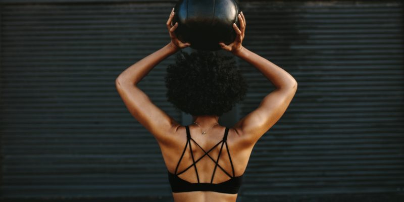 Woman holding exercise ball above her head