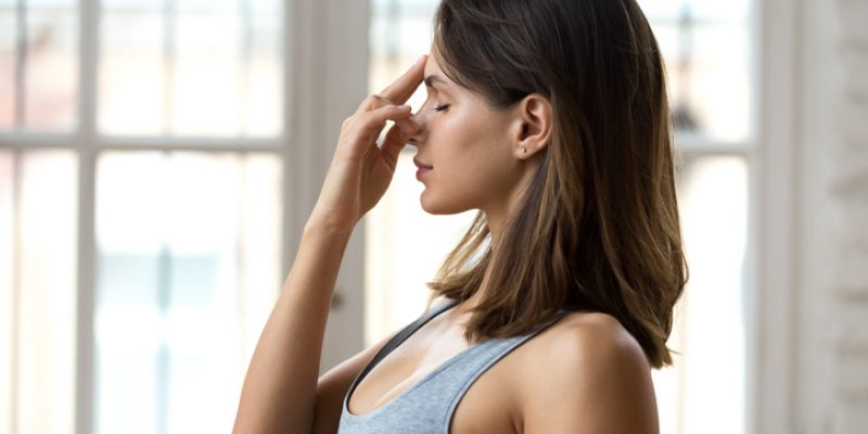 a woman practicing alternate nostril breathing during yoga