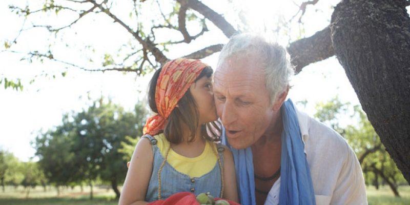 girl whispers in grandpas ear