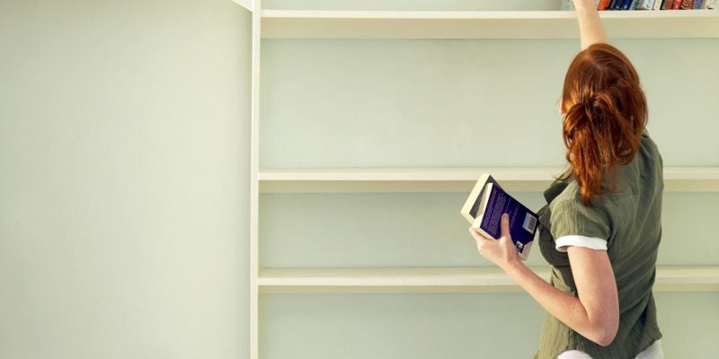 Woman putting things on shelf