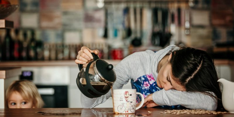 woman spilling coffee because of exhaustion coaxing adrenals