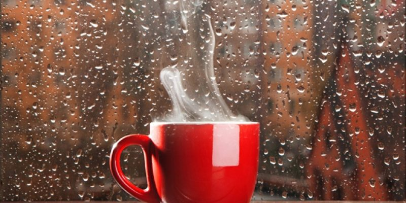 steaming coffee in rain covered window