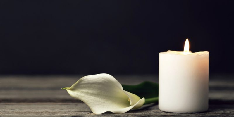 A lit candle and a calla lily as a ritual for death and grief