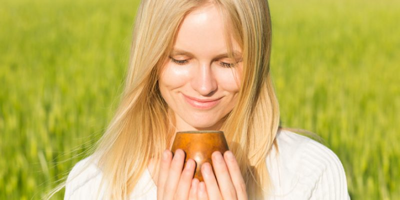 Happy woman drinking herbal tea for digestive health in late summer, Earth element