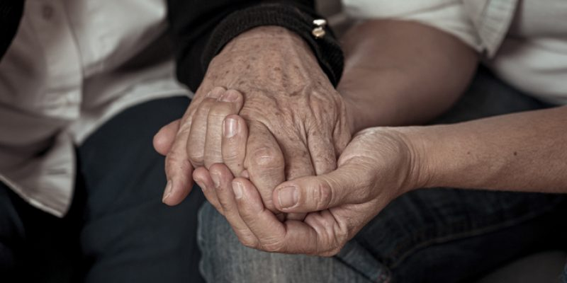 An elderly couple holding hands and being present