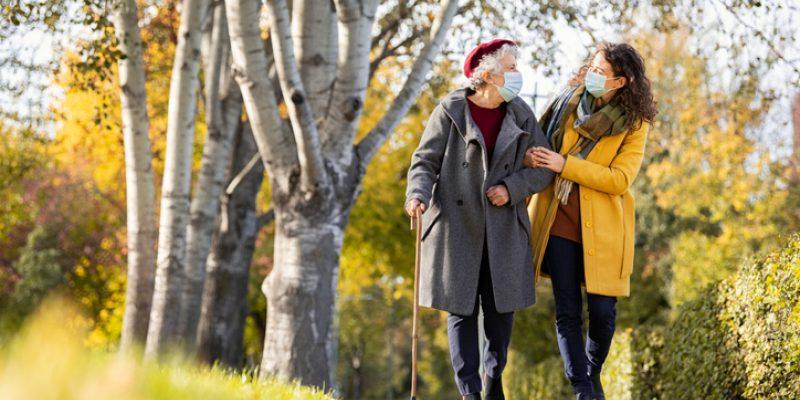 Two women walking in park wearing face masks