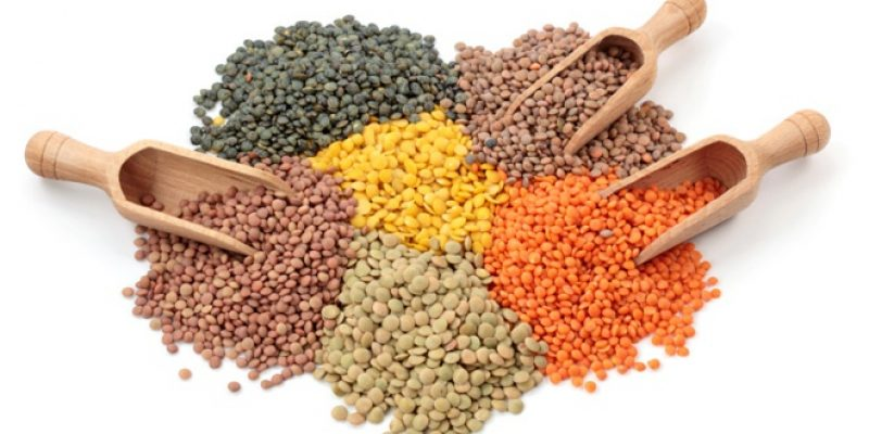 Variety of lentils and wooden spoons