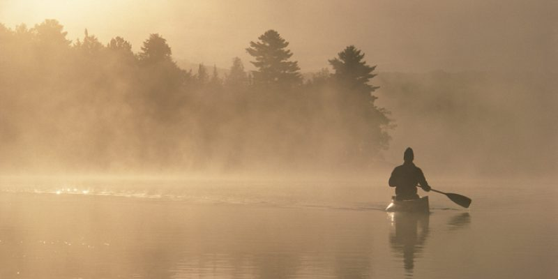 kayaking through fog and light on a lake
