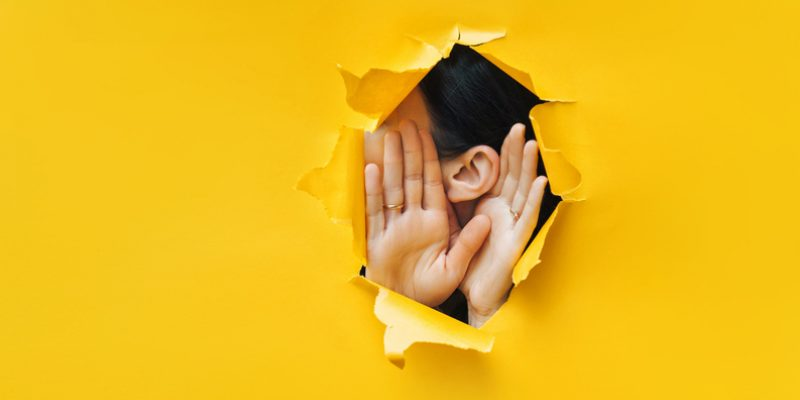 ear listening through hold in yellow wall