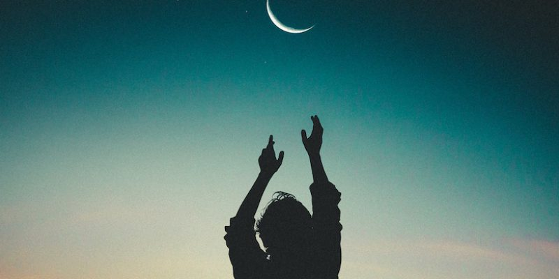 Silhouette of person reaching up to moon