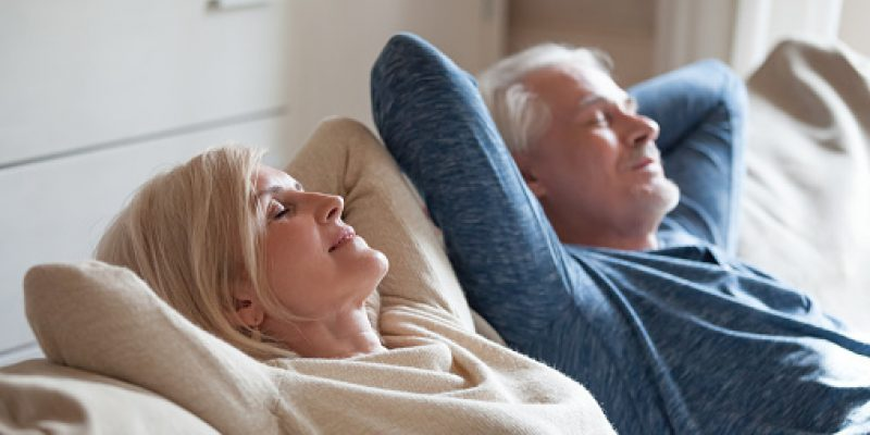 Calm mature couple relaxing on sofa together peacefully.