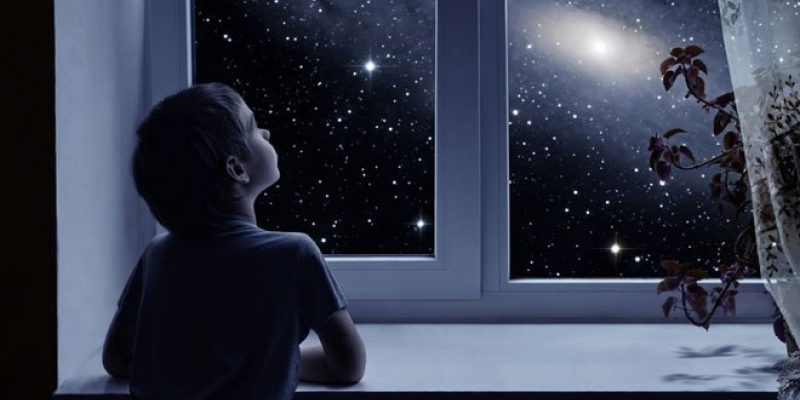 Child looking out dark window