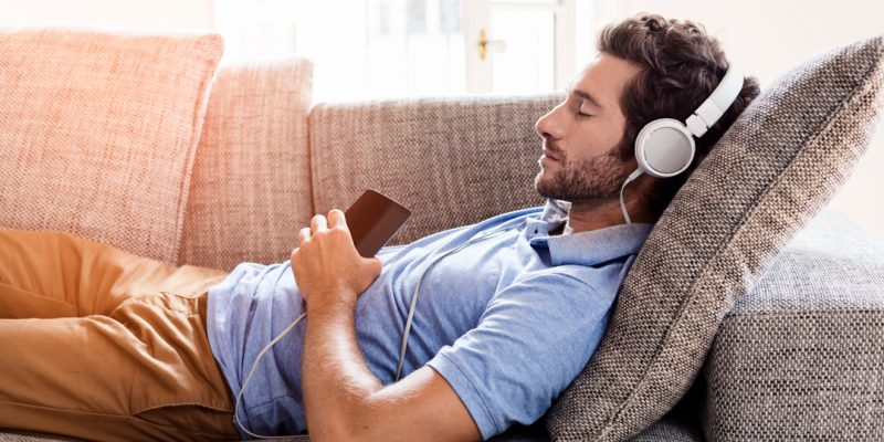Man lying on couch listening to music