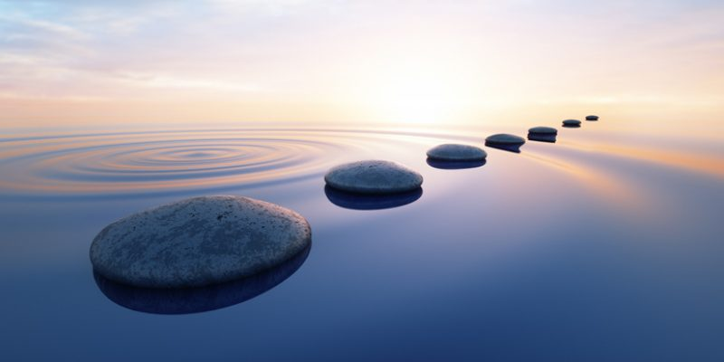 Pebbles in wild calm ocean to show spiritual enlightenment