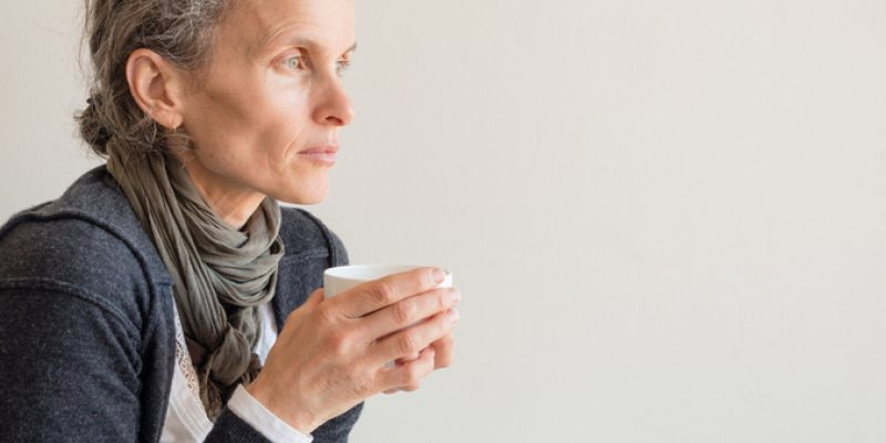 A pensive woman drinks coffee