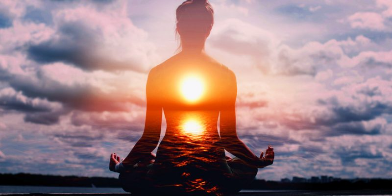 Woman meditating at sunrise awaken