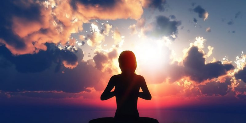 Graphic of woman meditating at sunset