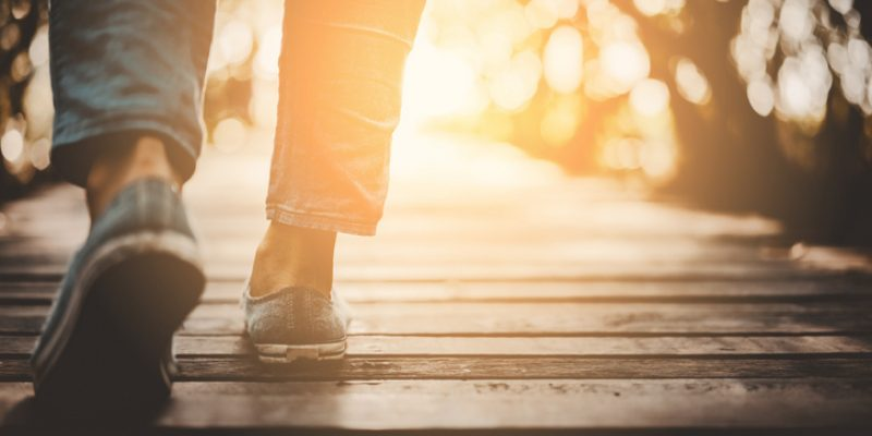 Image of person's feet, walking into sunset