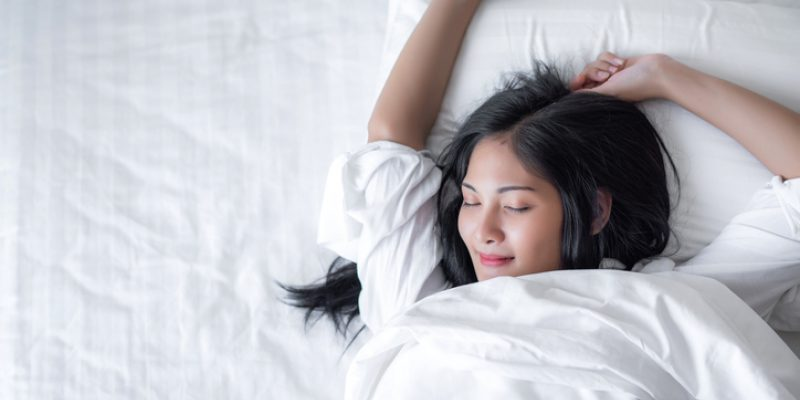 woman looking blissful sleeping in bed of white sheets