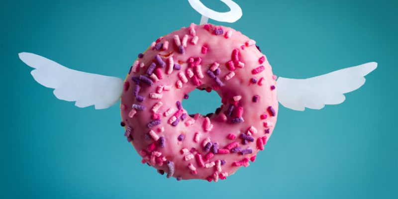 sweet pink donut with white paper wings and nimbus on a blue background