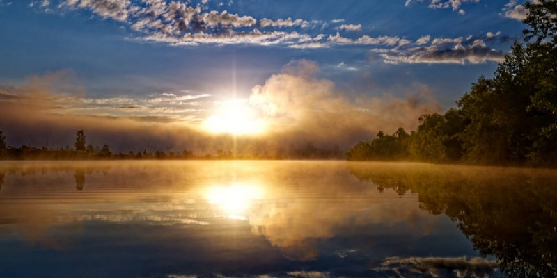 a sun rises over a lake giving a sense of hope