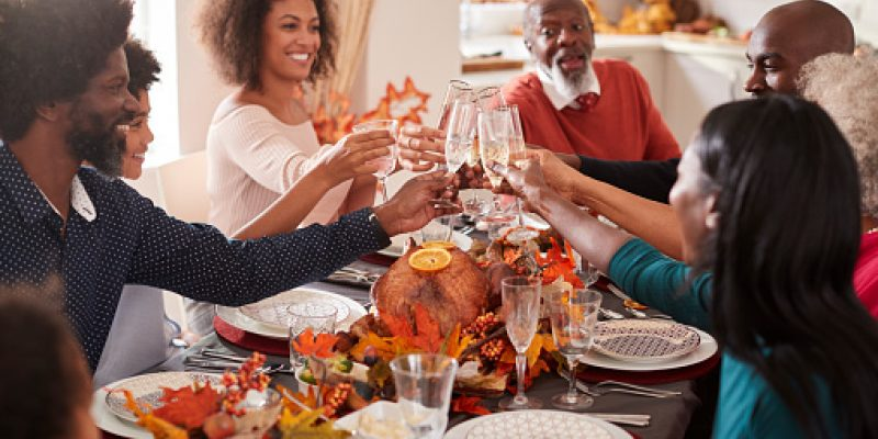 Multi generation mixed race family raise their glasses to make a toast at their Thanksgiving dinner table.