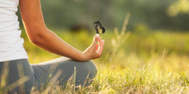 Woman meditating with butterfly landing on hand
