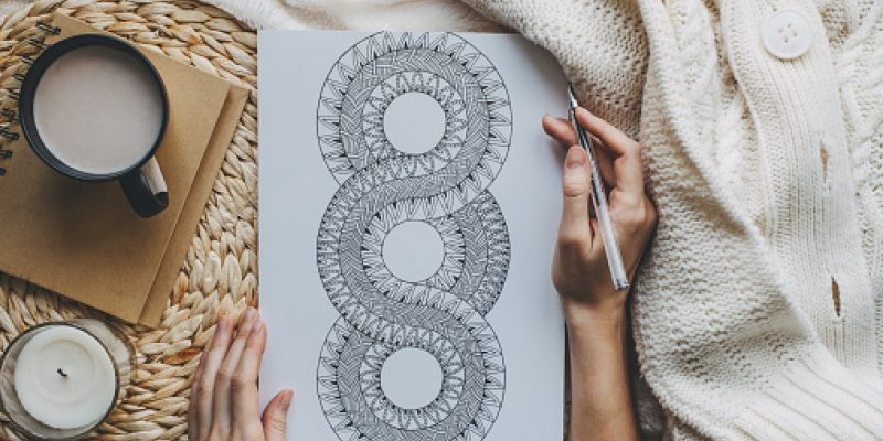 A woman's hand is drawing a mandala