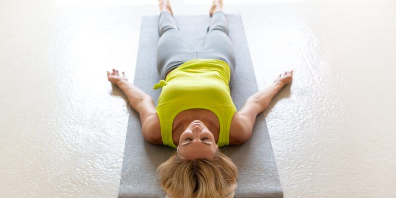 woman laying on mat yoga nidra transitional