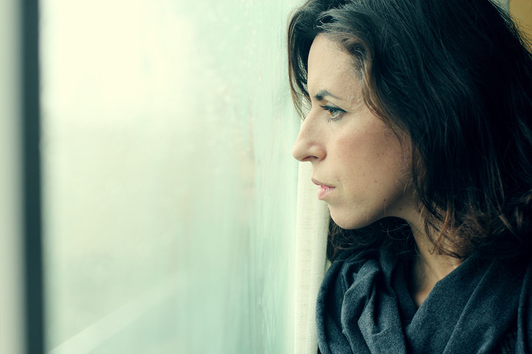 Serious woman looking out window