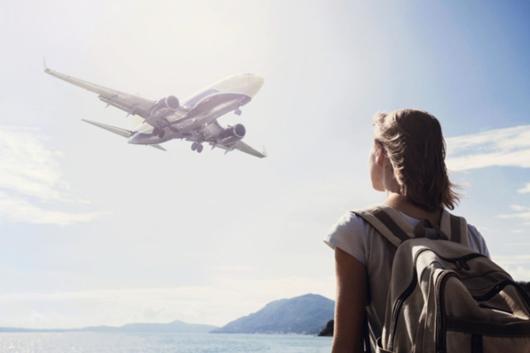 Girl watches plane in sky