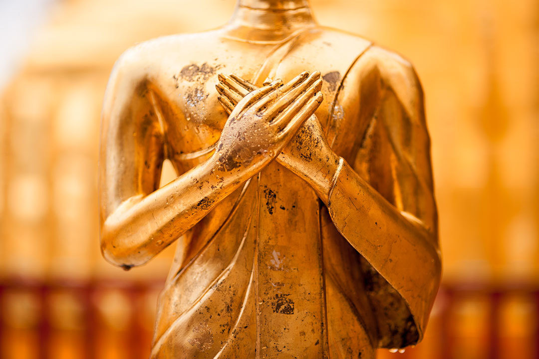 Buddha statue with hands on heart