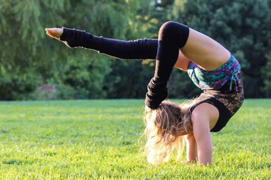 Woman in scorpion yoga pose variation