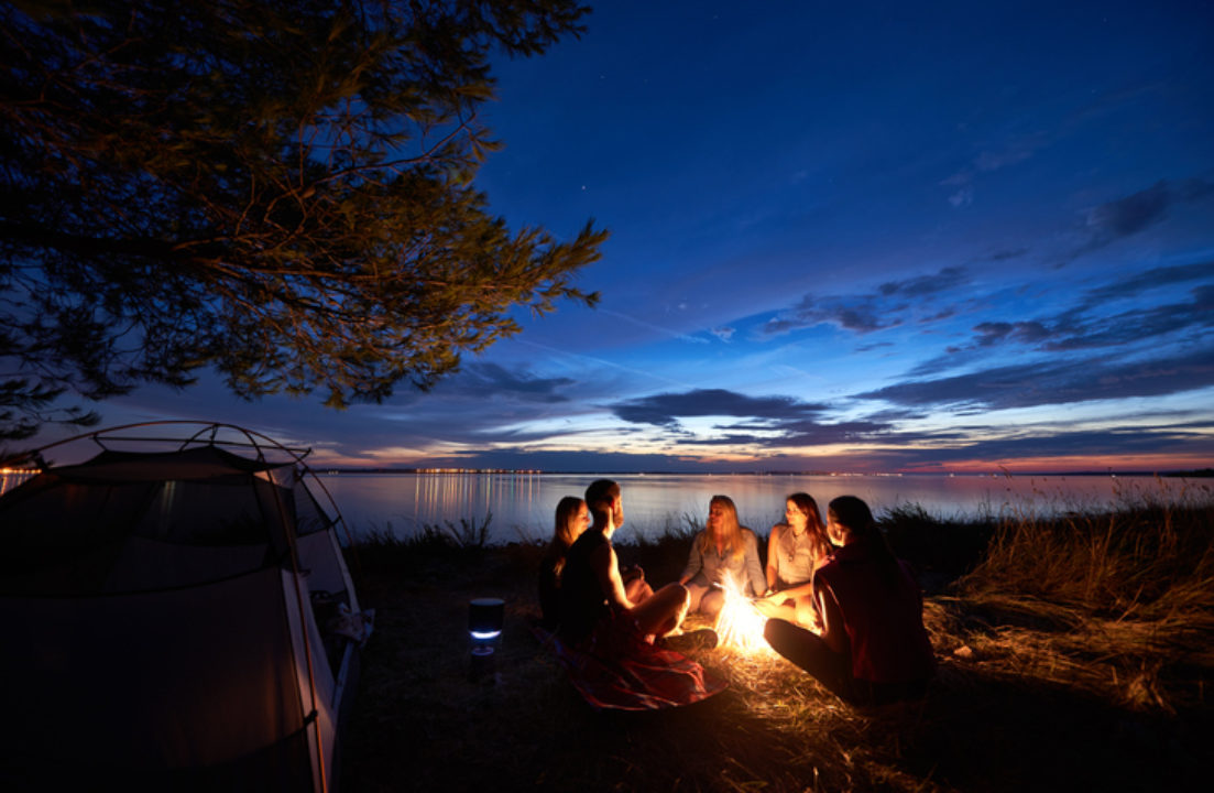 Group of people around campfire under evening sky.