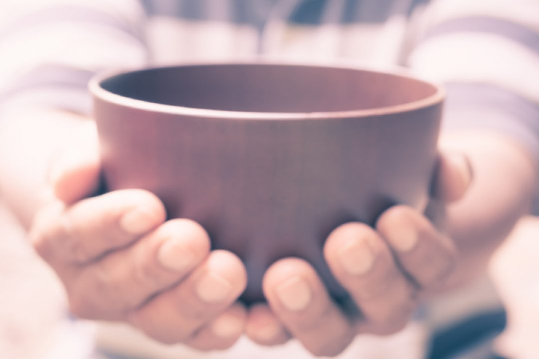 Two hands hold out an empty bowl, asking for help.