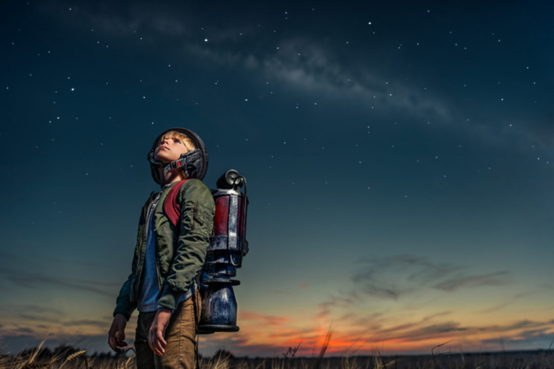 Boy looking at space with jet pack on