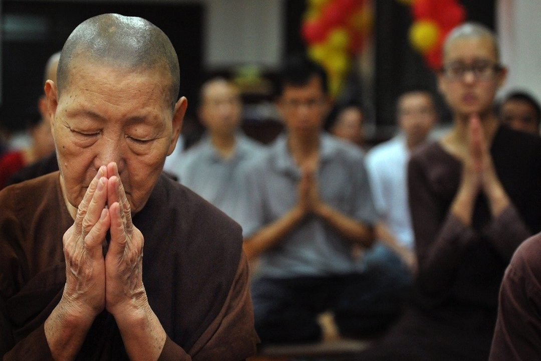 A Buddhist woman prays.