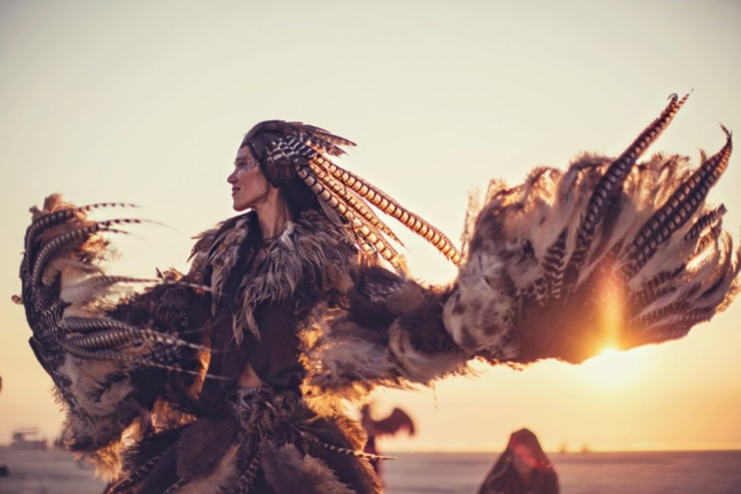Woman dancing with feathers at Burning Man